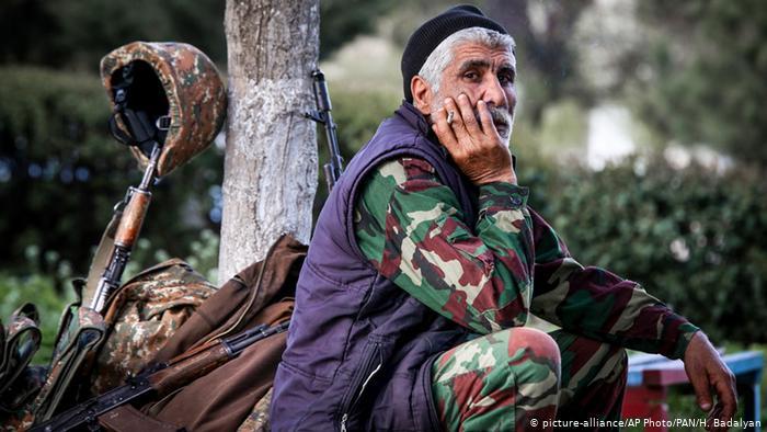 Человек, сидящий рядом с оружием