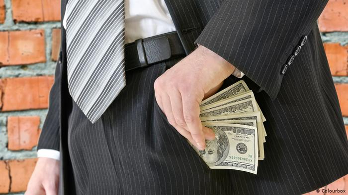Мужчина кладет пачку долларов в карман