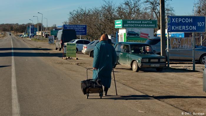 Пожилая женщина с сумкой идет в направлении Крыма в районе административной границы
