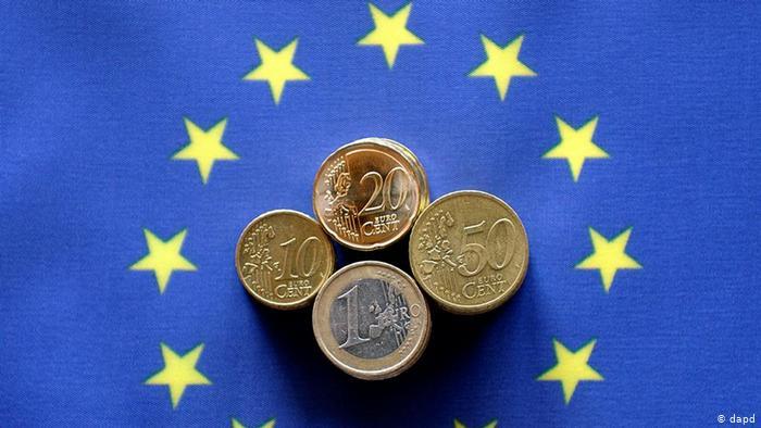 Монеты в 10, 20, 50 евроцентов и 1 евро на фоне флага Евросоюза