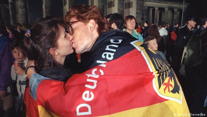 Покрытый флагом Германии молодой человек целует девушку у Бранденбургских ворот в Берлине