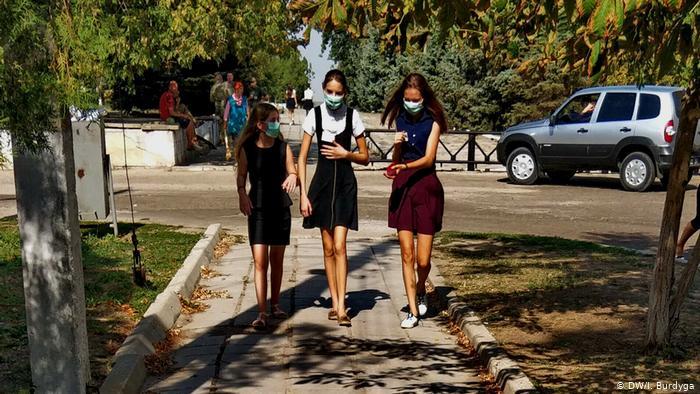 Школьницы из херсонского села Преображенка в защитных масках возвращаются домой после отмены занятий