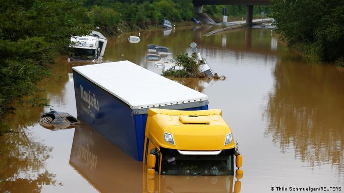 Грузовики и легковые машины под водой на улице в Эрфтштадте