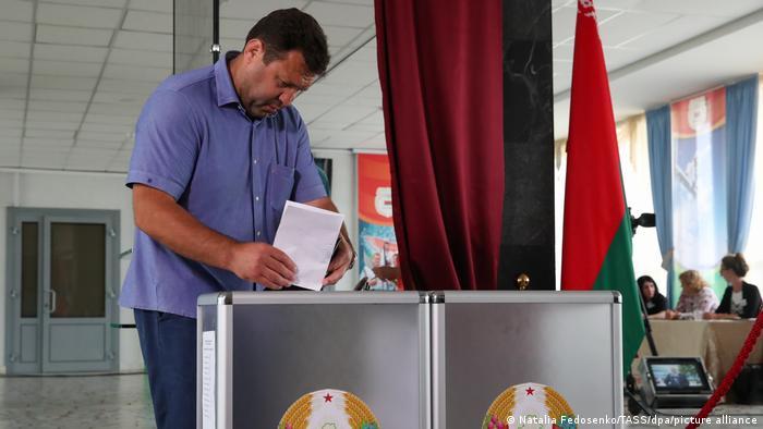 Мужчина бросает бюллетень в урну для голосования