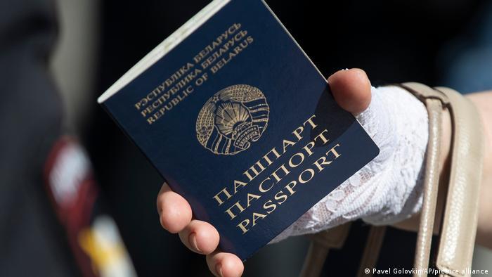 Женщина держит в руке паспорт Беларуси