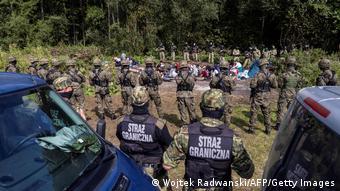 Мигранты из Афганистана в окружении польских пограничников
